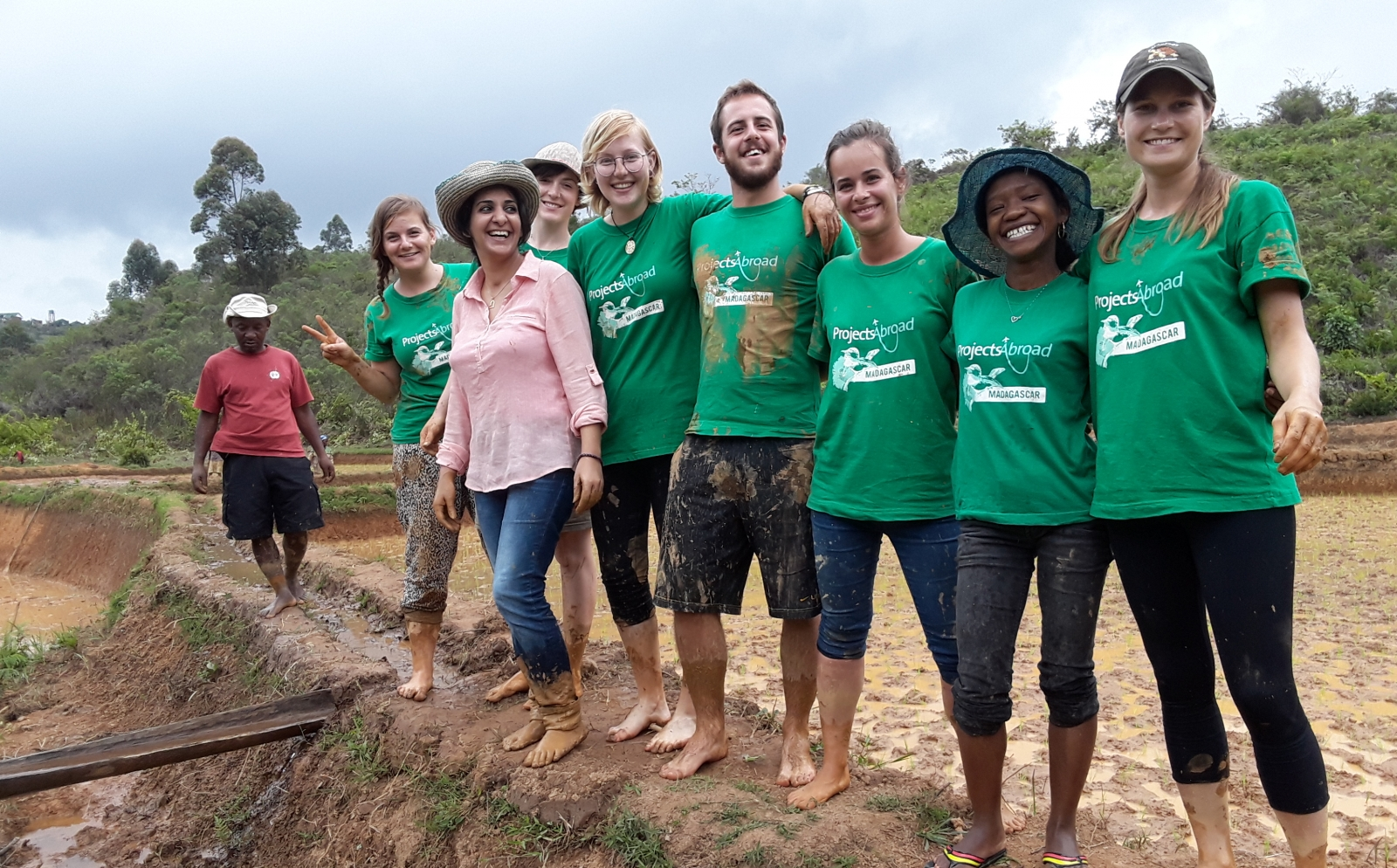 A group of muddy recent graduates take a break from planting rice in Madagascar during their volunteer abroad experience.